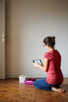 Woman kneeling beside decorating equipment, looking at digital tablet, rear view