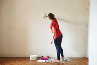 Woman painting wall using paint roller, rear view