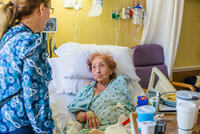 Patient on hospital bed talking to visitor