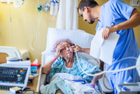 Hospital staff checking on patient on hospital bed