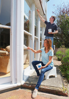 Couple painting window frame