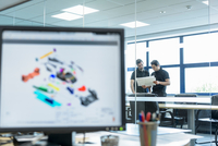 Engineers work with CAD design imagery in racing car factory
