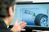 Engineer works with CAD design imagery in racing car factory, close up