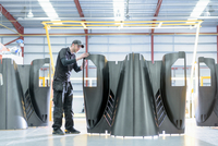 Engineer inspecting carbon fibre body parts in racing car factory