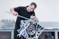 Engineer assembling engine in racing car factory