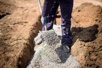 Builder shovelling gravel on housing building site