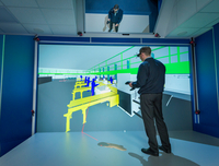 Engineer inspecting factory layout in 3D in virtual reality suite