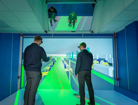 Engineers inspecting factory layout in 3D in virtual reality suite