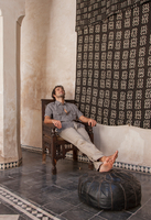 Man sitting with feet up on pouffe, Marrakesh, Morocco