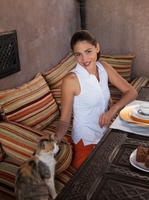 Woman at table stroking cat, Marrakesh, Morocco