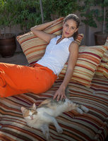 Woman with cat relaxing on cushions, Marrakesh, Morocco