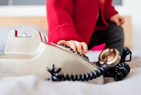 Cropped shot of baby girl dialling landline telephone