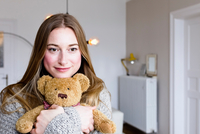 Portrait of mid adult woman in living room hugging teddy bear