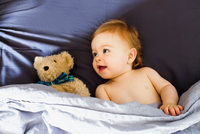 Baby girl lying in bed with teddy bear