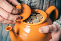 Close up of man's hands holding teapot full of coins