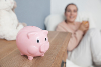 Mother sitting in baby nursery, piggy bank on chest of drawers