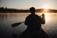 Senior man canoeing on lake at sunset, rear view