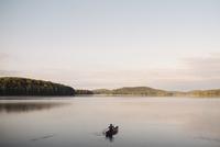 Senior woman canoeing on lake, rear view