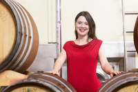 Portrait of young woman in wine cellar, beside wine barrels, smiling