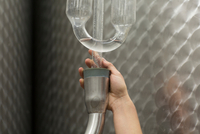 Hand of person checking air lock on fermentation tank in wine cellar