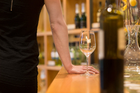 Cropped view of woman in wine shop with wine glass