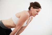 Woman in exercise studio wearing crop top bending forward
