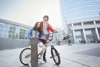 Girl and man with BMX and skateboard in urban area