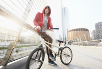 Man with BMX leaning against hand rail in urban area