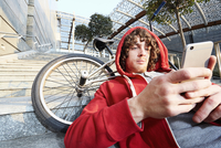 Man sitting on steps with BMX using smartphone