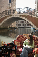 Young woman looking up from canal gondola, Venice, Italy