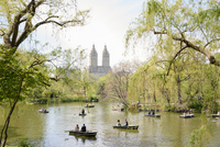 Tourists rowing boats on boating lake in Central Park, New York, USA