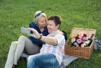 Mature couple on grass having picnic, taking selfie