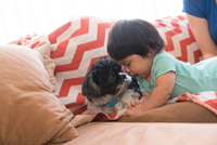 Baby playing with pet dog on sofa