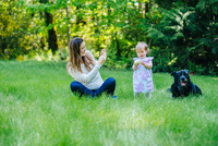 Woman photographing toddler daughter and labrador in park