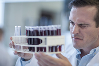 Mid adult man in laboratory, holding rack of test tubes