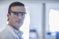 Portrait of mid adult man in laboratory, wearing safety goggles