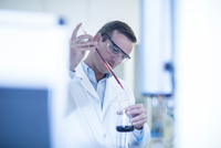 Mid adult man in laboratory, inserting liquid into glass flask