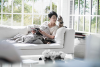 Woman reading on sofa with pet dogs