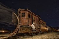 Ghostly man wearing hoody standing by abandoned old train