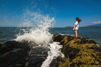 Young woman standing on rocks by ocean, Bowen Island, British Columbia, Canada