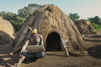 Man of the Mursi Tribe with laptop and kalashnikov gun, Omo Valley, Ethiopia