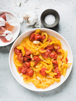 Pasta tagliatelle with cherry tomato sauce and garlic on white plate