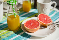 Halved grapefruit and bottle of orange juice