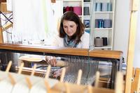 Young woman using loom 11015286962| 写真素材・ストックフォト・画像・イラスト素材|アマナイメージズ