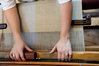 Hands of young woman using loom