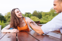 Young couple arm wrestling on picnic bench laughing 11015287007| 写真素材・ストックフォト・画像・イラスト素材|アマナイメージズ
