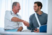 Doctor shaking hands with man in arm sling 11015287103| 写真素材・ストックフォト・画像・イラスト素材|アマナイメージズ