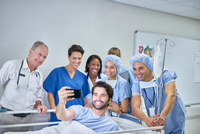 Patient in hospital bed taking selfie with doctors and nurses