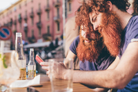 Young male hipster twins with red hair and beards reading smartphone texts at sidewalk bar