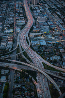 Aerial view of rush hour traffic on highway and flyover at dusk, Los Angeles, California, USA